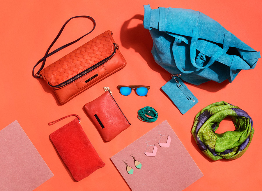 Womens bright colored accessories for summer in flat lay image.