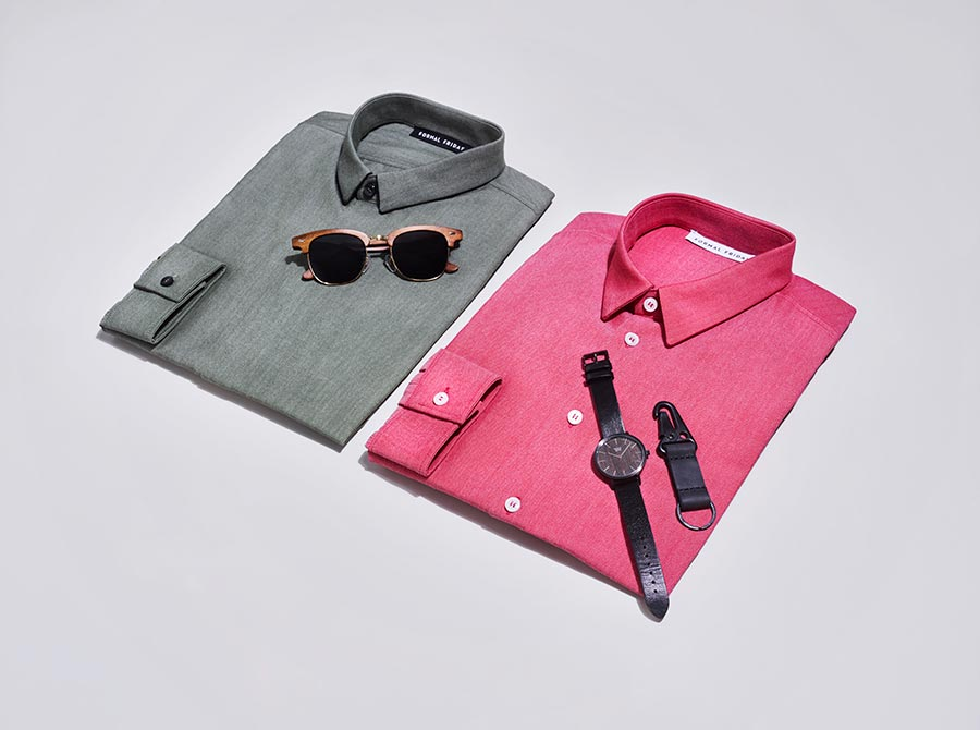 Men's shirts in flat lay image with sunglasses, a watch and other accessories.