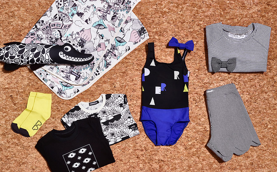 Sustainable kids fashion in flat lay image. Children's swimwear, jersey items and other summer fashion.