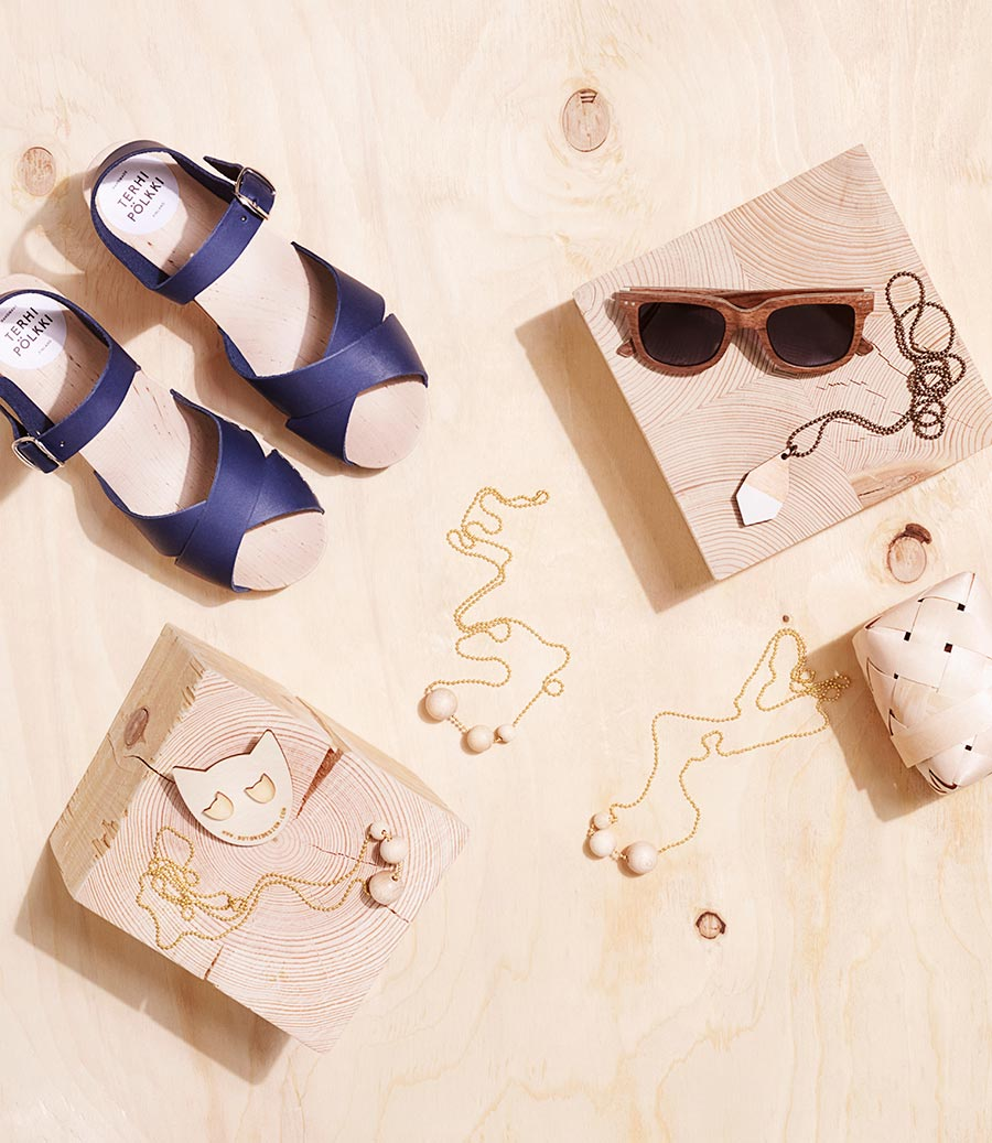 Women's summer accessories in flat lay. Jewellery, wooden shoes and sunglasses.