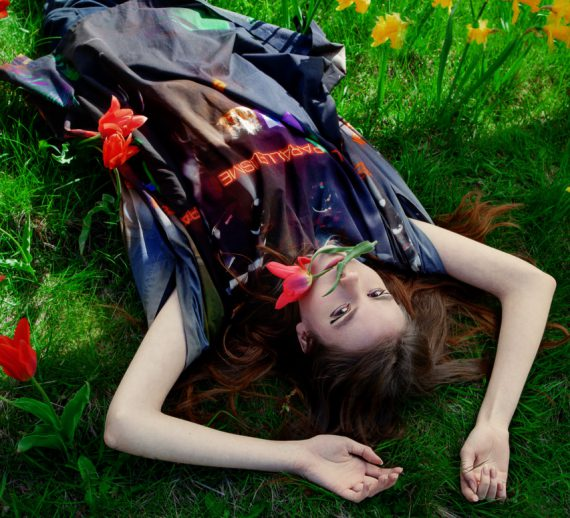 Fashion editorial with woman among tulips wearing a kaftan